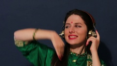 Young Indian woman listening to music on headphones Stock Footage