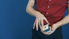 Close up conjurer in red shirt perform playing cards magic tricks Stock Footage