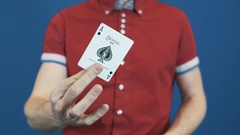 Close up magician in red shirt toss playing cards, show Ace of Spades to camera Stock Footage