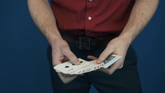 Close up conjurer in red shirt showing playing cards magic focuses Stock Footage