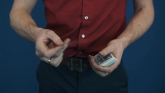 Close up illusionist in red shirt showing playing cards magic focuses Stock Footage