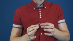 Close up illusionist in red shirt perform magic trick disappear in hands coin Stock Footage