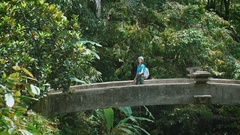 Female traveler in casual blue clothing turning on the bridge and holding selfie Stock Footage