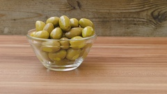 Delicious green olives on a wooden table Stock Footage