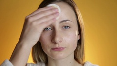 Woman cleansing face on a yellow background Stock Footage