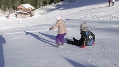Little girl running and sliding down the ski slope in winter time, SLOW MOTION Stock Footage