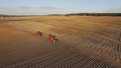 4K. Flight above freshly cultivated fields with agricultural machinery, aerial. Stock Footage
