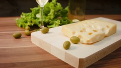 Piece of Maasdam cheese on a wooden board Stock Footage