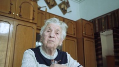 Portrait of old wrinkled tired alone grandmother looking and says at camera Stock Footage