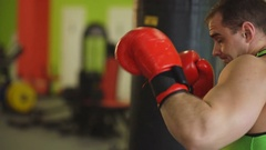 Young boxer man practicing on a punching bag with woman help Stock Footage
