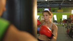 Young woman boxer hit punching bag during pre-match warm-up with her trainer in Stock Footage