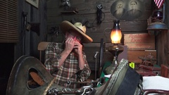 Cowboy Western, playing the harmonica in the bunkhouse Stock Footage