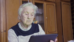Old woman and electronic tablet Stock Footage
