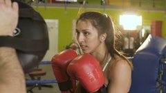 Slow motion of young woman boxer fight to her trainer during pre-match warm-up Stock Footage