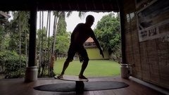 Island of Bali. The young guy trains on specially balance board. The man learns Stock Footage