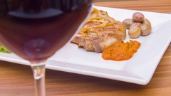 Glass of red wine and steak lying on a plate with tomatoes Stock Footage
