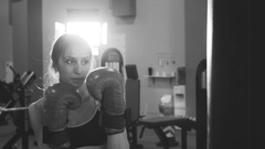 Slow motion of young woman boxer hit punching bag during pre-match warm-up in Stock Footage