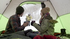 Cute Couple Warm Up In Tent With Hot Chocolate, Wave Hello To Snowboarder Friend Stock Footage