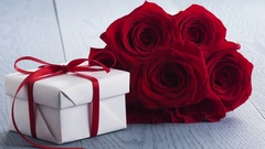 Seven red roses with gift box on blue table and falling petals in slowmo Stock Footage