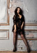 Fashion sexy young woman in black lacy lingerie and stockings posing on old wall Stock Photos