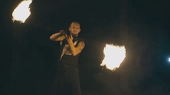 Brave muscular guy in a fire show at night Stock Footage