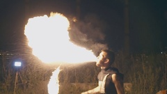 Young muscular guy breathes fire at night Stock Footage