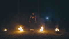 Daring muscular guy in a fire show at night Stock Footage