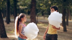 Children eating cotton candy. Boy and girl in the park eating cotton candy. boy Stock Footage