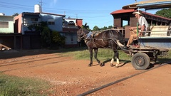 Water-carrier horse-drawn carriage at a railway crossing. Trinidad, Cuba Stock Footage