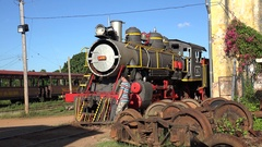 Tourist inspects the steam locomotive in the Trinidad depot. Cuba Stock Footage