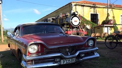Retro Ford car in the Trinidad depot with the steam locomotive on bkg. Cuba Stock Footage