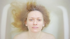 Close-up of a woman without make-up, lying in the bath. Stock Footage