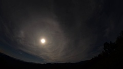 Full moon underneath which outpaced white clouds over the dark hills Stock Footage
