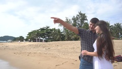 Young happy couple hug each other on the beach ang looking at the sea. Honeymoon Stock Footage