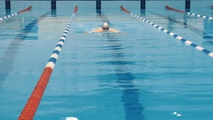 Professional swimmer in cap breathing performing the butterfly stroke Stock Footage