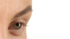 Girl with poor vision puts lens and flashes. Close up. White background Stock Footage