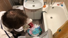 Man throws his dirty laundry in the washing machine Stock Footage