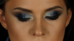 Beautiful girl with makeup breath taking looks straight and blinks his eyes Stock Footage