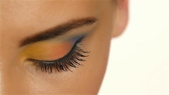 Girl with gray eyes with beautiful make up and a sharp eye looking up. Closeup Stock Footage