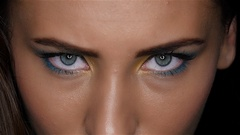 Girl with a beautiful bright make up and sharp eyes looking intently up. Close Stock Footage