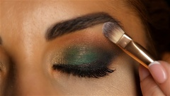 Girl with an evening make up with closed eyes, make up brush tints eyelid. Close Stock Footage