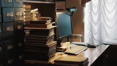 Square computer monitor on table with pile of books in old archive interior Stock Footage