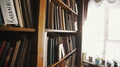 Dolly shot bookshelves in old style library interior. Russian text, flowerpots Stock Footage