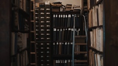 Dolly shot interior of old library bookshelves with document folders Stock Footage