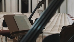 Close up dolly cellos and music stands on scene in classical style concert hall Stock Footage