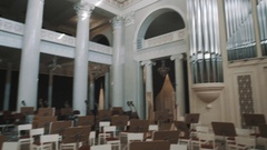 Panoramic shot from organ to empty seats in large classic music hall Stock Footage