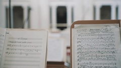 Close up focus pull of note sheets on music stands in concert hall Stock Footage