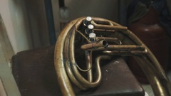 Close up dolly shot part of brass tuba with three buttons laying on chair Stock Footage