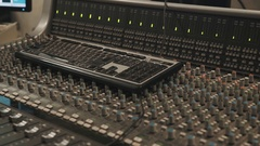 Close up of computer keyboard laying on music mixing console Stock Footage