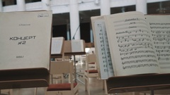 Dolly shot of music stands on scene of music hall with note sheets on them Stock Footage